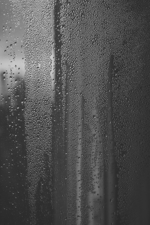 Water drops on the window. Droplets or drops of water on misted glass.