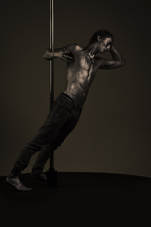 Pole dance. Man with nude torso covered with shimmering paint, dark background.