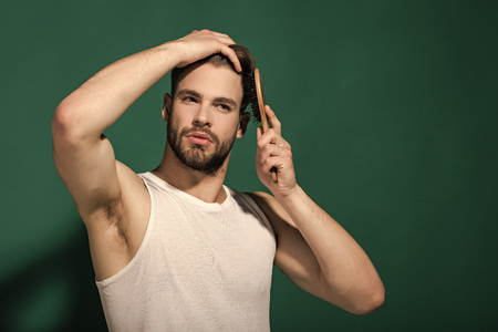 Glamur man hair style. Macho with bearded face and haircut in white singlet