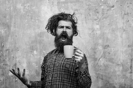 Morning coffe. singing bearded man pulling stylish fringe hair with blue cup