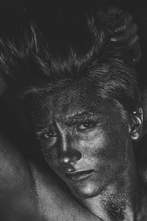 Glamur man hair style. Fashion and art concept. Man covered with shimmering silver paint