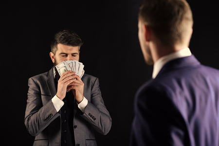 Business succsses. Man with beard on calm face sniffing money, smell of profit. Meeting of reputable businessmen, black background. Business payment concept. Businessmen, business partners counting profit