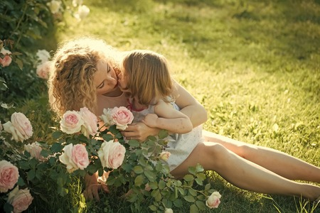 Child Childhood Children Happiness Concept. Mom kissing daughter on green grass on sunny summer day
