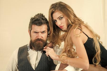 Beauty salon. Hair care. Woman with razor, scissors cut hair of man.