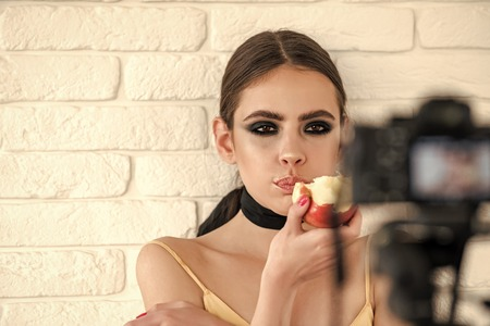 cinematographic process. Woman with smokey eyes eat apple and look in camera