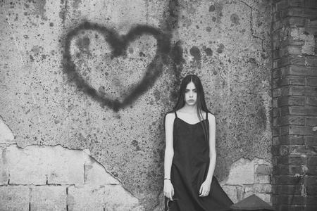 Love hurts. Girl posing with heart graffiti on grey wall 写真素材
