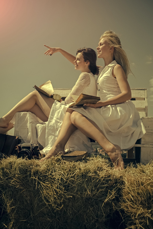Happy lesbian couple. Women in straw wreaths and white dresses