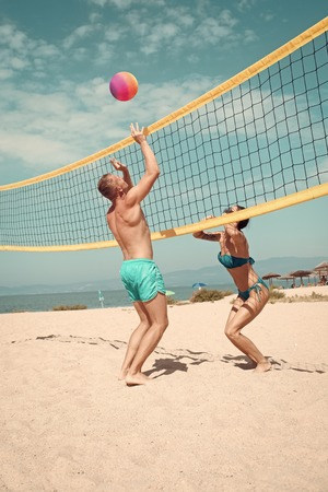 beach games. Beach volleyball concept. Couple have fun playing volleyball. Young sporty active couple beat off volley ball, play game on summer day. Woman and man fit, strong, healthy, doing sport on beach.