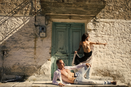 Sexy couple. Woman with breasts, man with torso lies outdoor. Couple enjoys nudity. Sexy couple undressing under sunlight with ancient rocky wall and old door on background. Passion and concept.