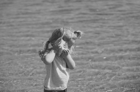childrens holiday. Boy listen to shell on sea beach Standard-Bild - 102597594