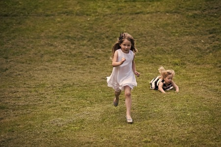 Kids playing - happy game. Kids run and fall on green grass on summer day Stok Fotoğraf