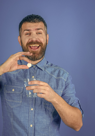 Men potency. Man with beard hold water glass on blue background, headache.