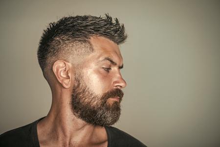Barbiere. Stile di capelli. Uomo con profilo del viso barbuto e capelli alla moda Archivio Fotografico