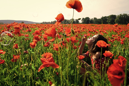 Drug, opium, narcotics. Woman blow bubble in poppy field, dreams, wishes.