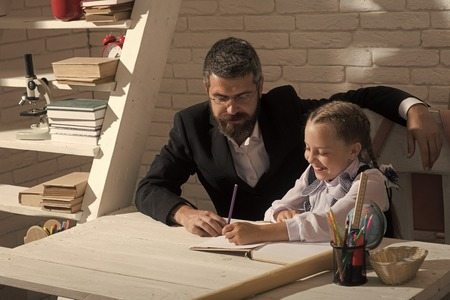 Home schooling. Kid and man sit by desk with school supplies