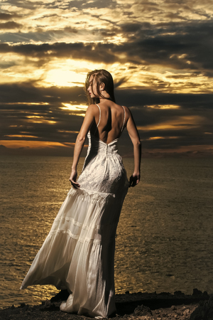 dating service. Pretty girl in white dress stands at dark sea shore