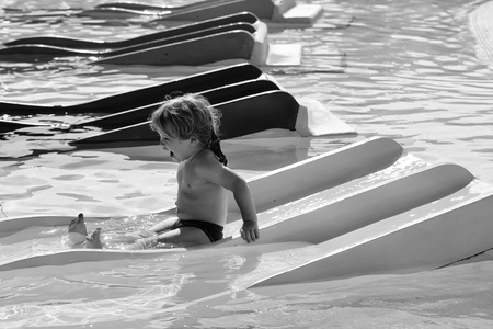 entertainment in the water park. Happy cute baby boy slides from blue waterslide