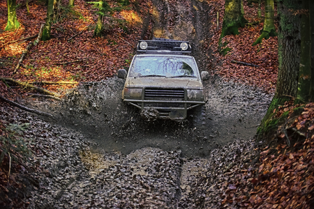 racing on off-road cars. SUV covered with mud stuck in dirt on path Stock Photo