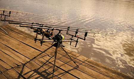 fishing equipment. Reels and rods at river or lake water.