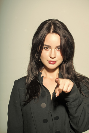 Attention, focus, advertising, direction, indication. Girl or woman with long brunette hair point finger