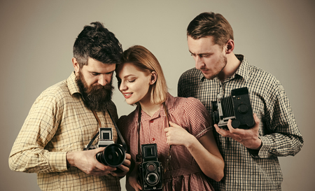 school of photography. Men, woman on concentrated faces looks at camera, grey background. Men in checkered clothes, retro style. Vintage photography concept. Company of busy photographers with old cameras, filming, working
