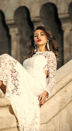 bride in a wedding dress. Girl in white dress sits on old stone handrails