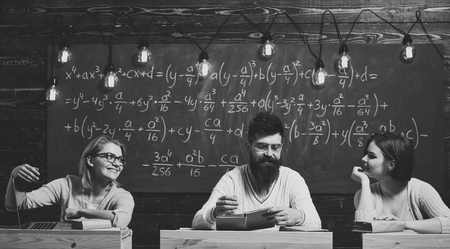College and education concept. Students, young scientists fall in love with professor chalkboard background. Girls, happy students looking with adoration at bearded teacher, lecturer, professor Stock Photo