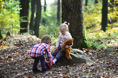 Little boy put shoes on girl feet. Brother help sister to put red boots. Helping hand concept. Children getting ready for walk in autumn forest. Childhood friendship, love and trust