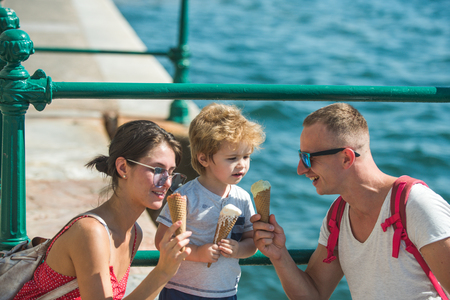 Summer vacation of happy family. Mother and father with son eat ice cream at sea. Child with father and mother. Family travel with kid on mothers or fathers day. Love and trust as family values.