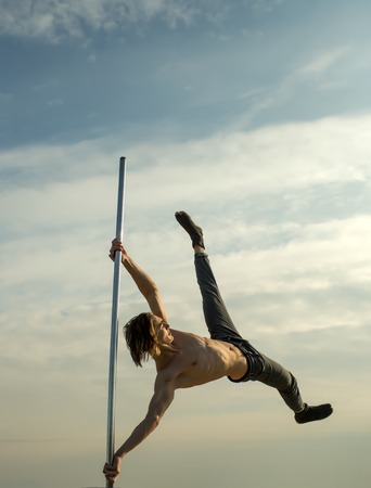 Strong man dancer workout on pole. man on pylon look far away on blue sky.