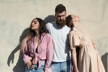 Man with beard hugs two ladies on hot sunny day. Girls turned to opposite sides while man hugs them. Love triangle concept. Threesome suffers of heat on summer day, wall on background Stock fotó - 104382409