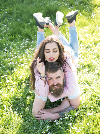 Lovely couple lying on grassy meadow, relationship and marriage concept. Bearded man chewing tiny flower while his wife smokes cigarette. Sensual brunette with closed eyes on top of her boyfriend