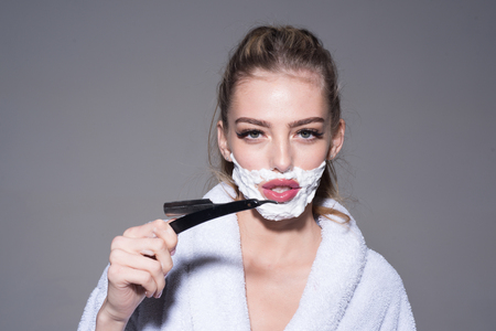 Blond woman with impudent look wearing white bathrobe isolated on gray background. Morning shaving, young female with foam on her face holding cut-throat razor Фото со стока