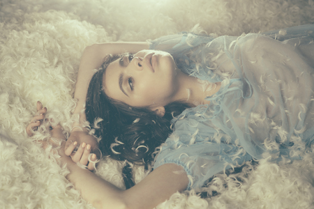 Dreamy girl lying on downy heap of white feathers. White fluff gently embracing young beautiful female in blue dress, bedtime fantasy concept.