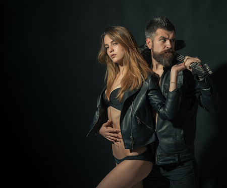 Couple in love cuddling with guitar, black background. Rock and roll concept. Couple and brutal posing with guitar. Guitarist with beard and girl in bra enjoy rock and roll lifestyle