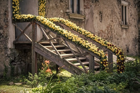 floral decoration. Front porch with flower decor. Old house and floral arrangement. Decoration, ornament, design. Freshness and withering concept.