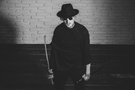 brutal tattooed man with a sword. Warrior in black sunglasses, hat and clothes, top view Stock Photo