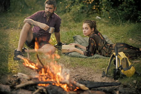 outdoor recreation by the fire. Couple of hikers relax at bonfire on nature Фото со стока