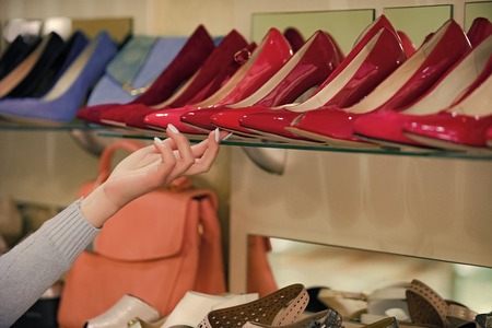 shelf in the shoe store. shop assistant hand with shopping showcase with female footwear