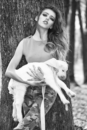 fashion model posing on camera. Stylish girl with goat in forest