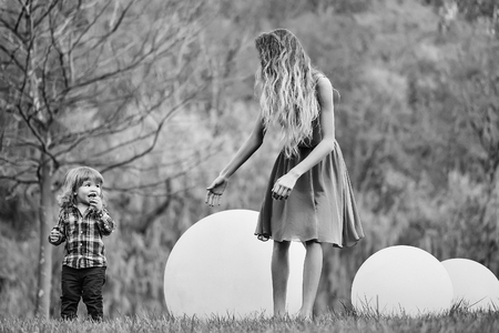 mom with a child in the park for a walk. Woman and boy with bog ball Фото со стока