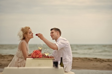 Romantic dinner by the sea. Wedding couple eating on beach