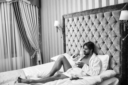 suite in the hotel. bearded man on bed with coffee 版權商用圖片