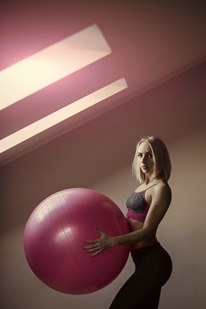 exercises for women with the ball. Girl athlete in sportswear with pink fitball
