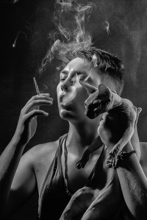 fashion portrait of a man with a cat. Smoking guy and Sphynx cat