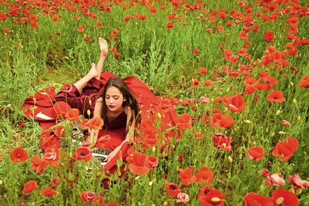 poppy field. Woman writer in poppy flower field. Reklamní fotografie - 102874075