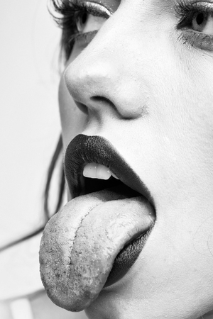woman shows the tongue. Sexy female lips Standard-Bild