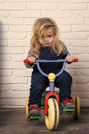 Boy riding bicycle in room. Child and tricycle Stock Photo