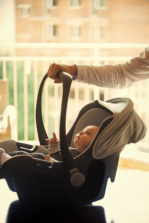 motherhood. Mothers love. Hand hold car seat with infant child on blurred background 版權商用圖片