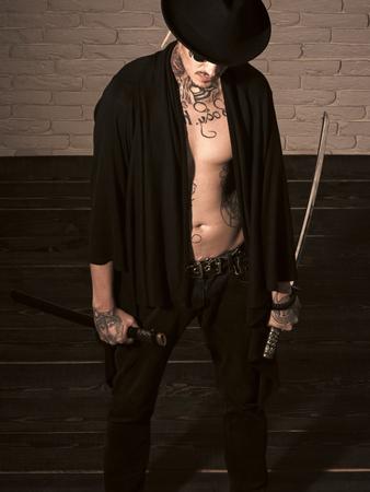 Man with sword standing on wooden floor, top view. Samurai, buddhist concept
